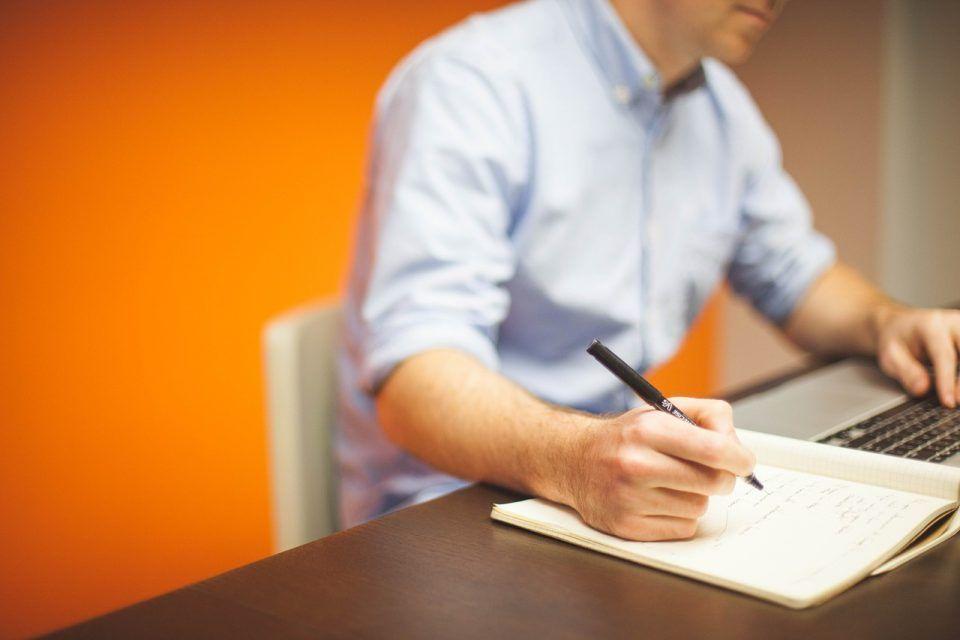 Man schreibt auf ein Papier über Büroimmobilien